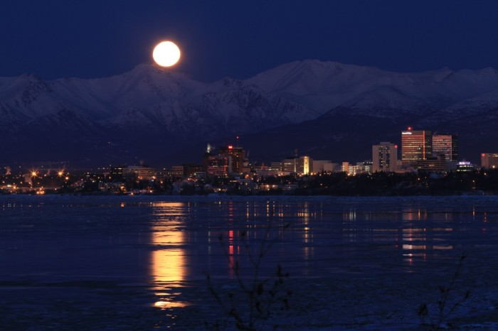 A full moon rises over the mountains Chugachskimi, reflected in the waters of Cook Inlet, near Anchorage, Alaska,