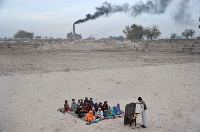 Afghan schoolchildren take lessons in an open classroom at a refugee camp on the outskirts of Jalalabad