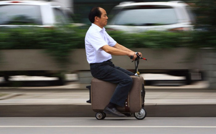 He Liang rides his home-made suitcase vehicle along a street in Changsha