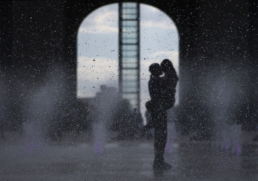 A couple stands in the rain