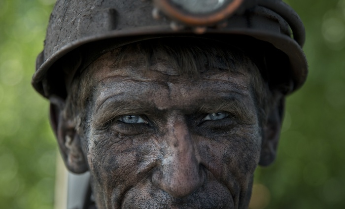 A Ukrainian coal miner waits for a bus after finishing his shift at a coal mine outside Donetsk, Ukraine