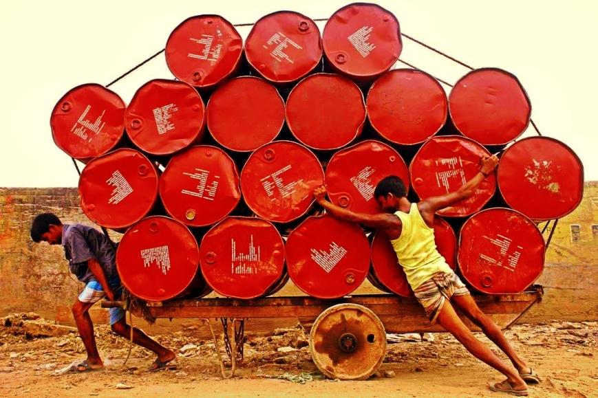 Two laborers haul barrels on a wooden cart in Dhaka, Bangladesh