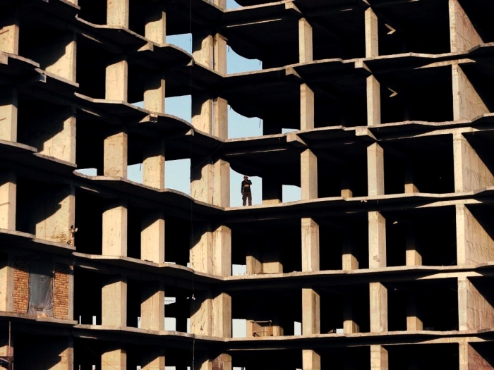 A worker stands at the site of an under-construction residential complex in Kabul, Afghanistan