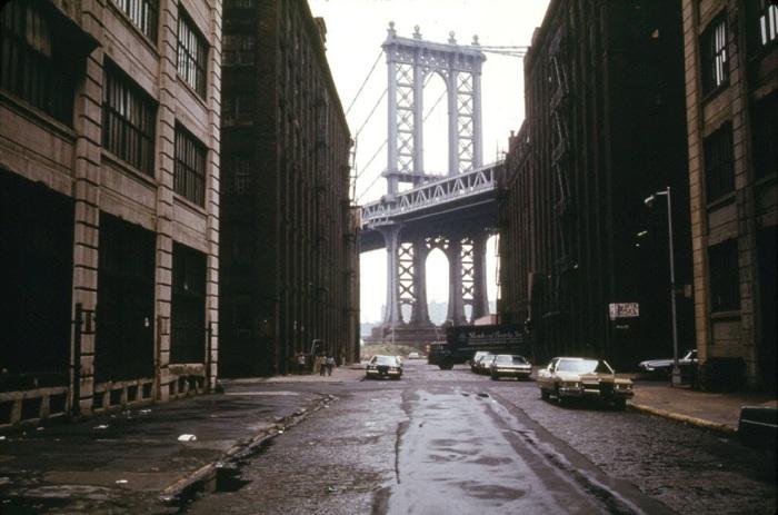 Manhattan Bridge tower in Brooklyn, New York City, framed through nearby buildings, in June of 1974