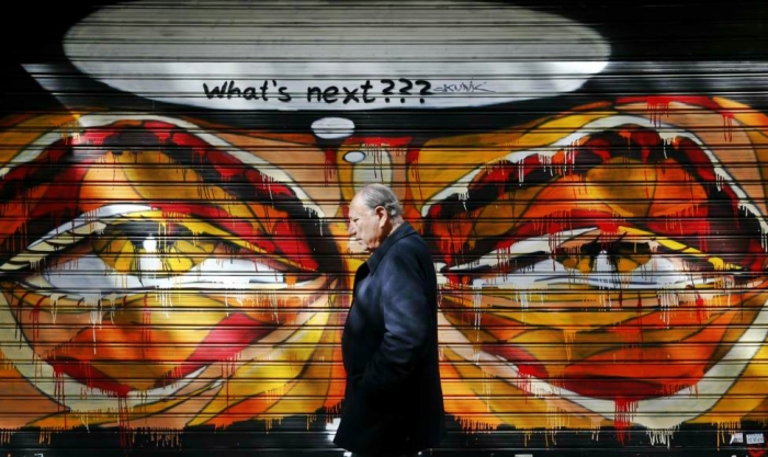 A man walks past graffiti in Athens. Germany's Finance Minister Wolfgang Schaeuble said on Wednesday it had not been an easy decision for euro zone finance ministers to extend the Greek rescue plan by four months.