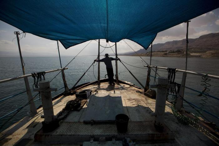 A researcher from the Israeli Geological Institute of Limnological Research sails on the research ship Taglit, during their monthly research of the Dead Sea water level near the Dead Sea coastal resort of Ein Gedi, Israel.